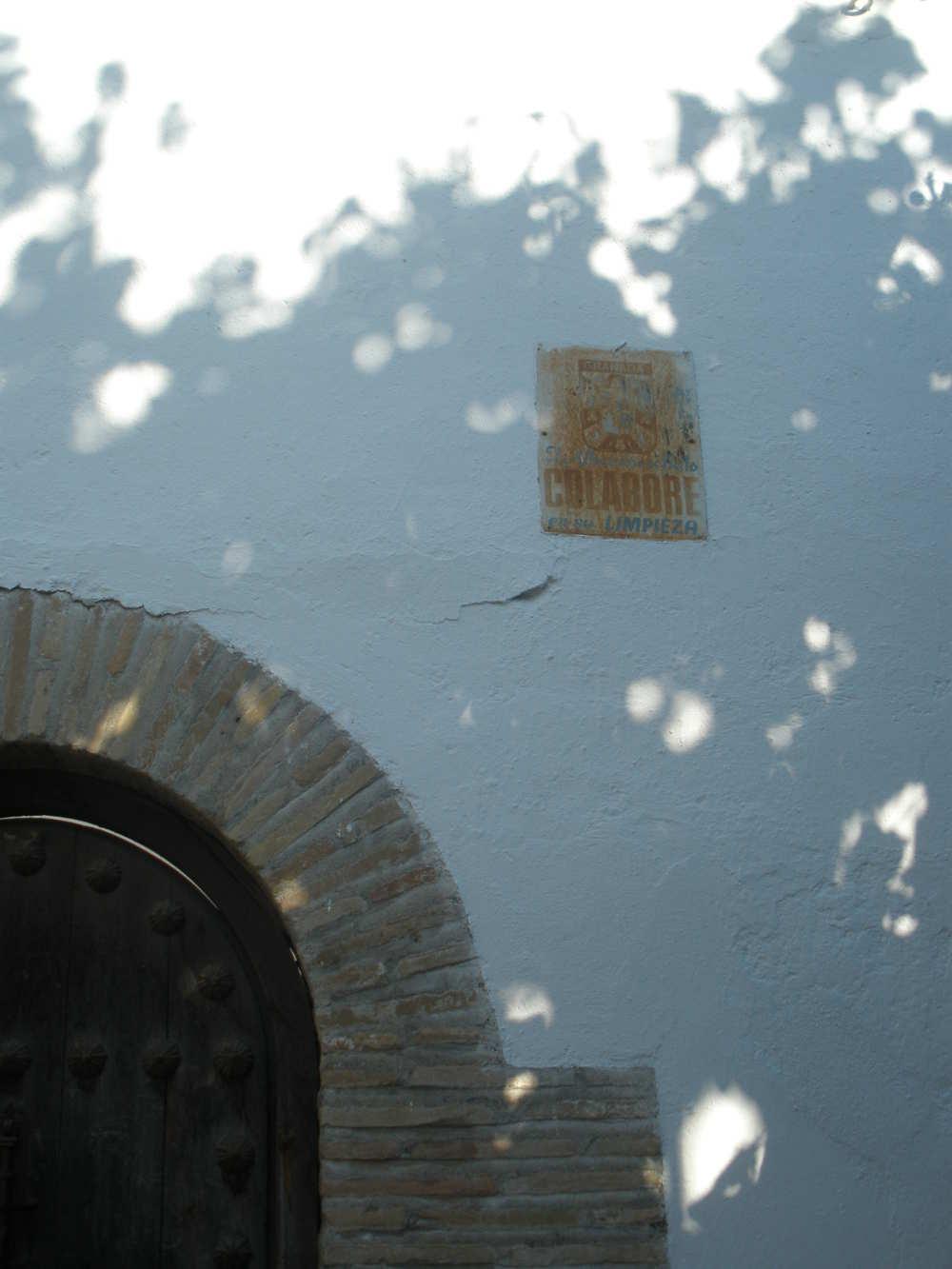 """Señal para colaborar en la limpieza del barrio, dice: El Albayzin es bello, colabore con su limpieza"""", situada en la fachada del Palacio de los Córdova en la entrada de la Cuesta del Chapiz"""