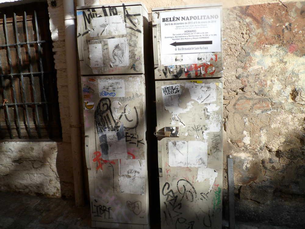 Señales con carteles manuales junto a carteles y pintadas de todo tipo en la Carrera del Darro esquina de la calle Zafra.