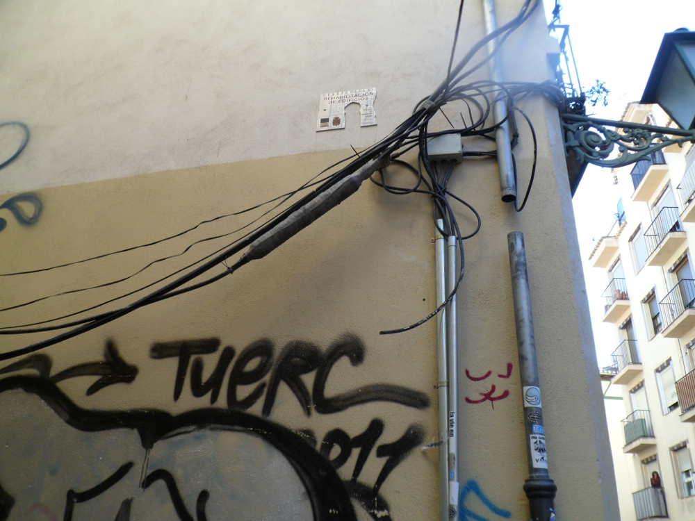 Señal de casa rehabilitada en el programa de Rehabilitación Elvira-Gómerez, junto al cableado y pintadas en Molino de la Corteza