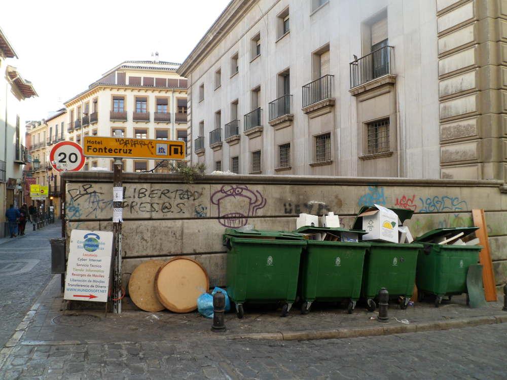 Señalización de hotel con el cartelón del locutorio y junto a los contenedores de basura en Elvira esquina Barrecheguren sin faltar las pintadas en la parte trasera del Banco España.