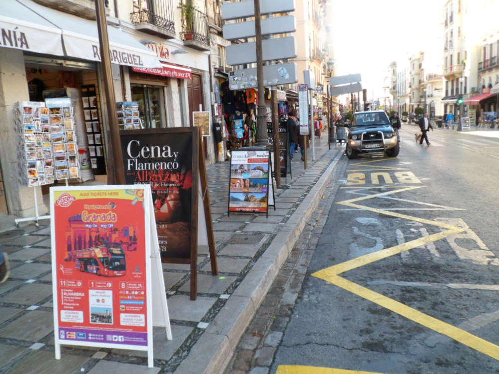 La señalización con cartelones comerciales ocupan la vía pública en la parada del tren turístico. También puede verse la señal de parada del bus y la ocupación comercial de la acera. Plaza Nueva