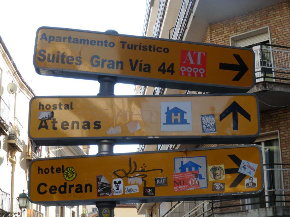 Señalización hotelera adornada con toda clase de pegatinas en calle Elvira esquina a Cedrán.