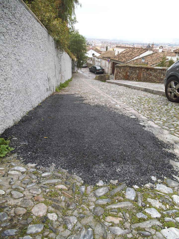 Los baches en el empedrado se rellenan de asfalto en la calle Zenete.  2014