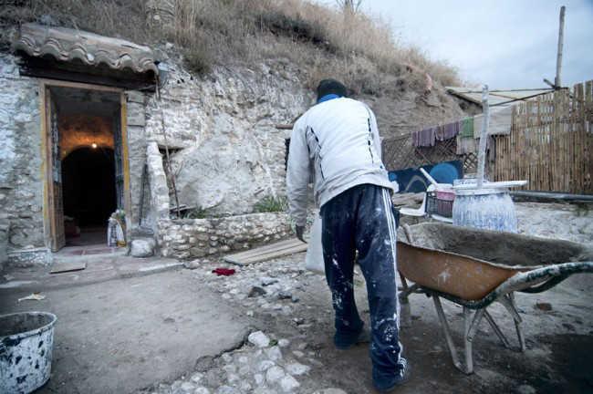 Un ciudadano subsahariano realiza obras para adecentar la cueva donde se aloja. Foto: JESÚS OCHANDO