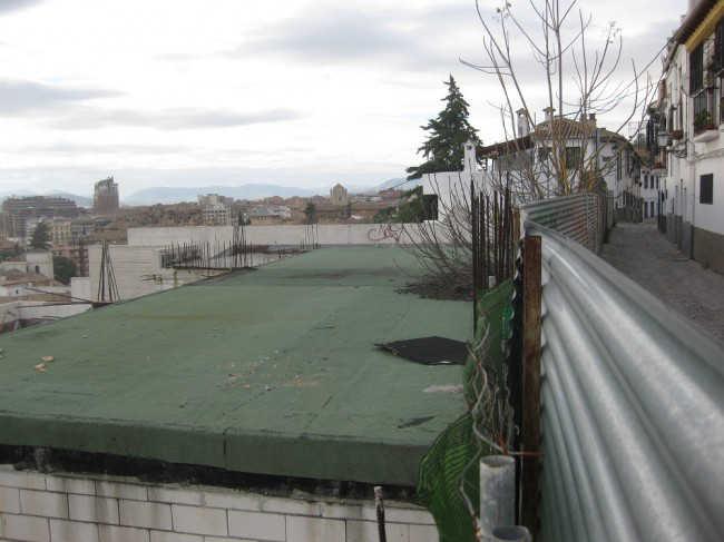 Estado del techo del aparcamiento que se quiere impermeabilizar y el vallado de chapa que se quiere sustituir.