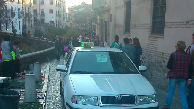 Taxis libre pasando por la Carrera del Darro el fin de semana mientras el transporte público no puede pasar. 2014