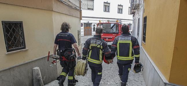 Tres bomberos vuelven al camión atascado en san Juan de los Reyes tras apagar el incendio. :: A. AGUILAR