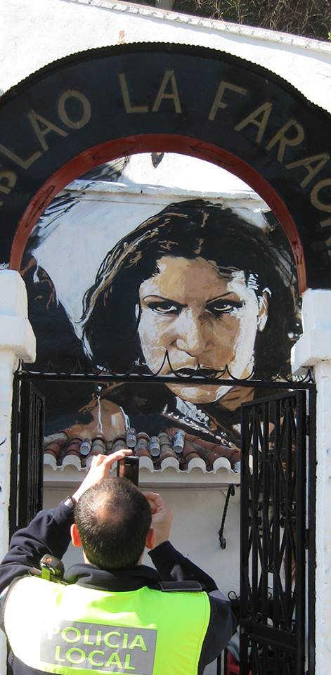 Uno de los agentes de la Policía Local fotografía el grafiti inacabado de Carmen Amaya, en el Sacromonte.