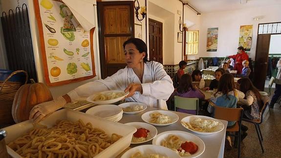 Una empleada del comedor del colegio Gómez Moreno prepara los platos. / GONZÁLEZ MOLERO