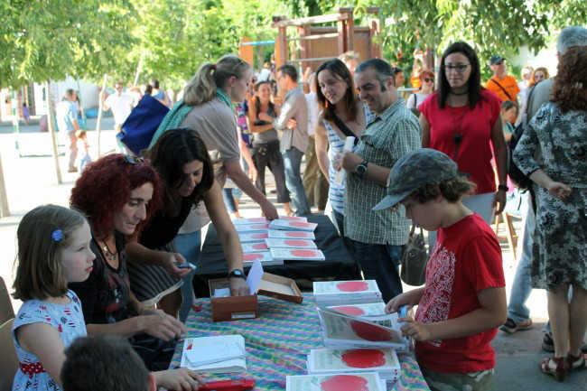 Un niños se interesa por el libro de recetas editado por las madres y padres de alumnos. GiM 2014