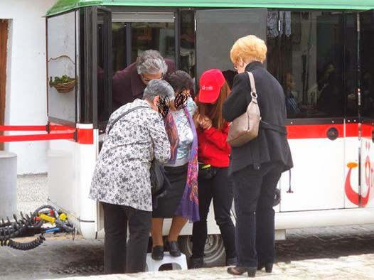 Una persona mayor necesita la banqueta de plástico y la ayuda de varias personas para bajar del tren turístico.