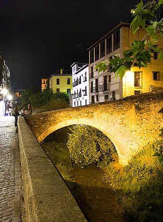 El río Darro y los monumentos de la Carrera del Darro iluminados anteriormente.