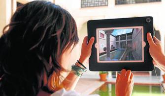Una pareja de visitantes hacen uso del Ipad en el patio para contemplar a través de la pantalla cómo era una casa tipo nazarí basada en Zafra.