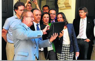 El alcalde en funciones, Juan Antonio Mérida, utiliza el Ipad ante la mirada del resto de autoridades. GH 2014