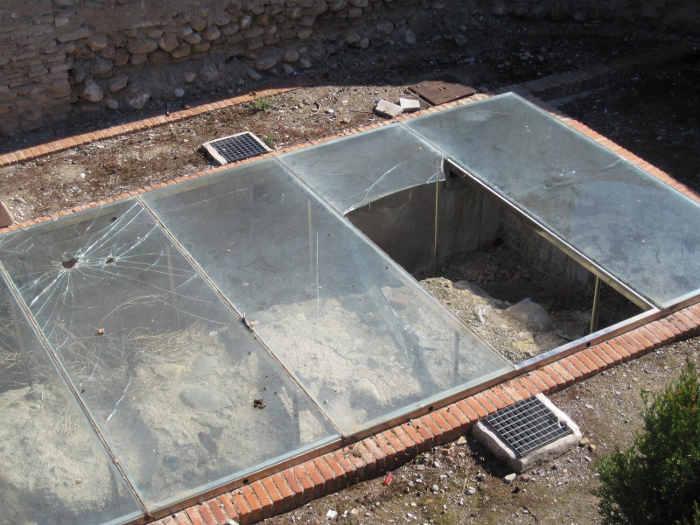 Estado del metacrilato que recubre los restos de muralla en el Huerto del Carlos tras el vandalismo a base de pedradas. 2010