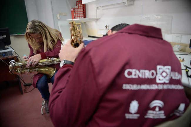 Alumnos limpian y afinan instrumentos. Foto J.M. Grimaldi-Oficina de Prensa de la Junta de Andalucía.