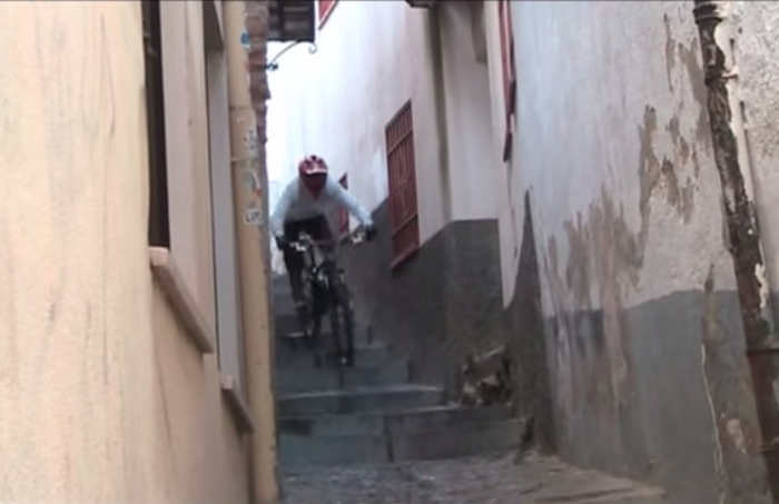 Ciclista en descenso por Rueda Bolas, una calle sinuosa y estrecha sin visibilidad.