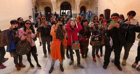 Un grupo de turistas fotografía la Alhambra. / m. zarza