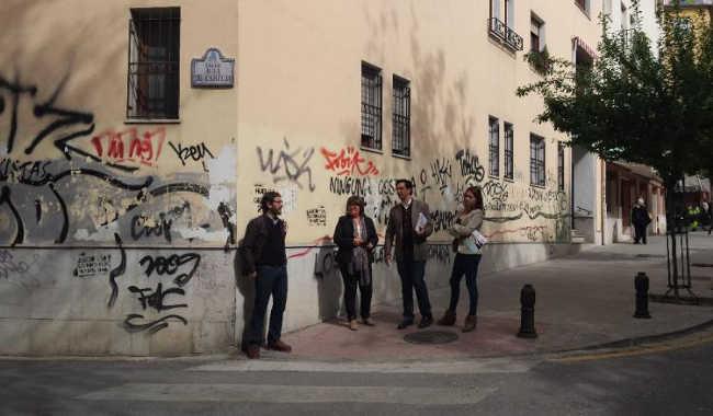 Concejales del PSOE ante unas pintadas en la calle Real de Cartuja.
